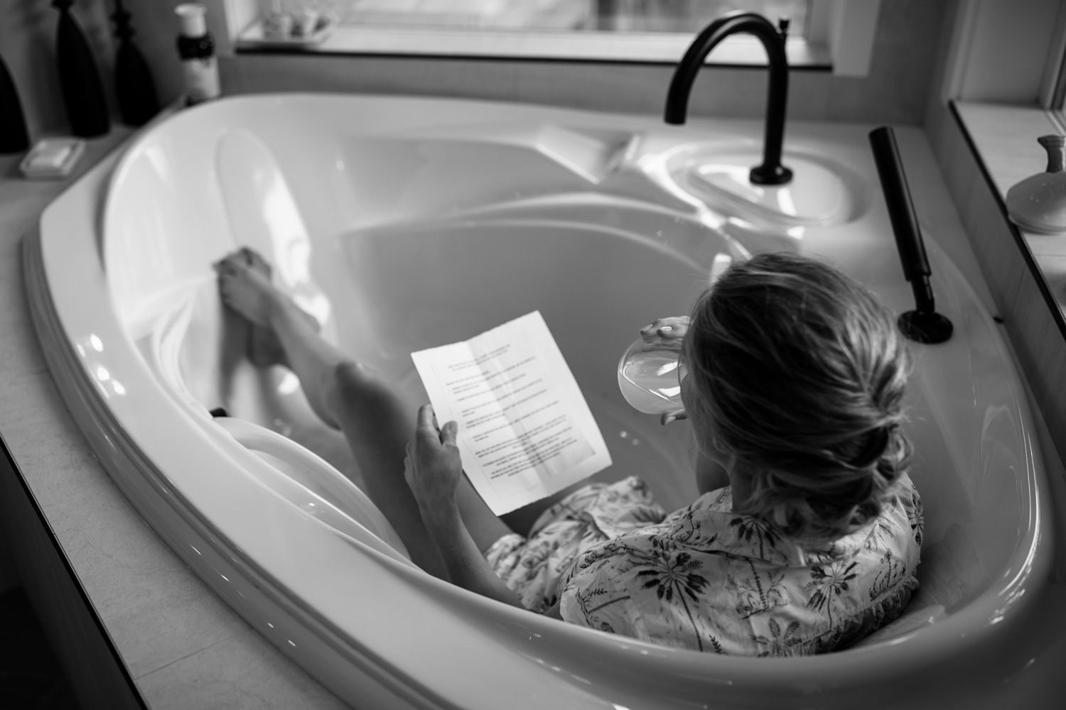 Candid photo of bride drinking wine and reading through her vows in the bath