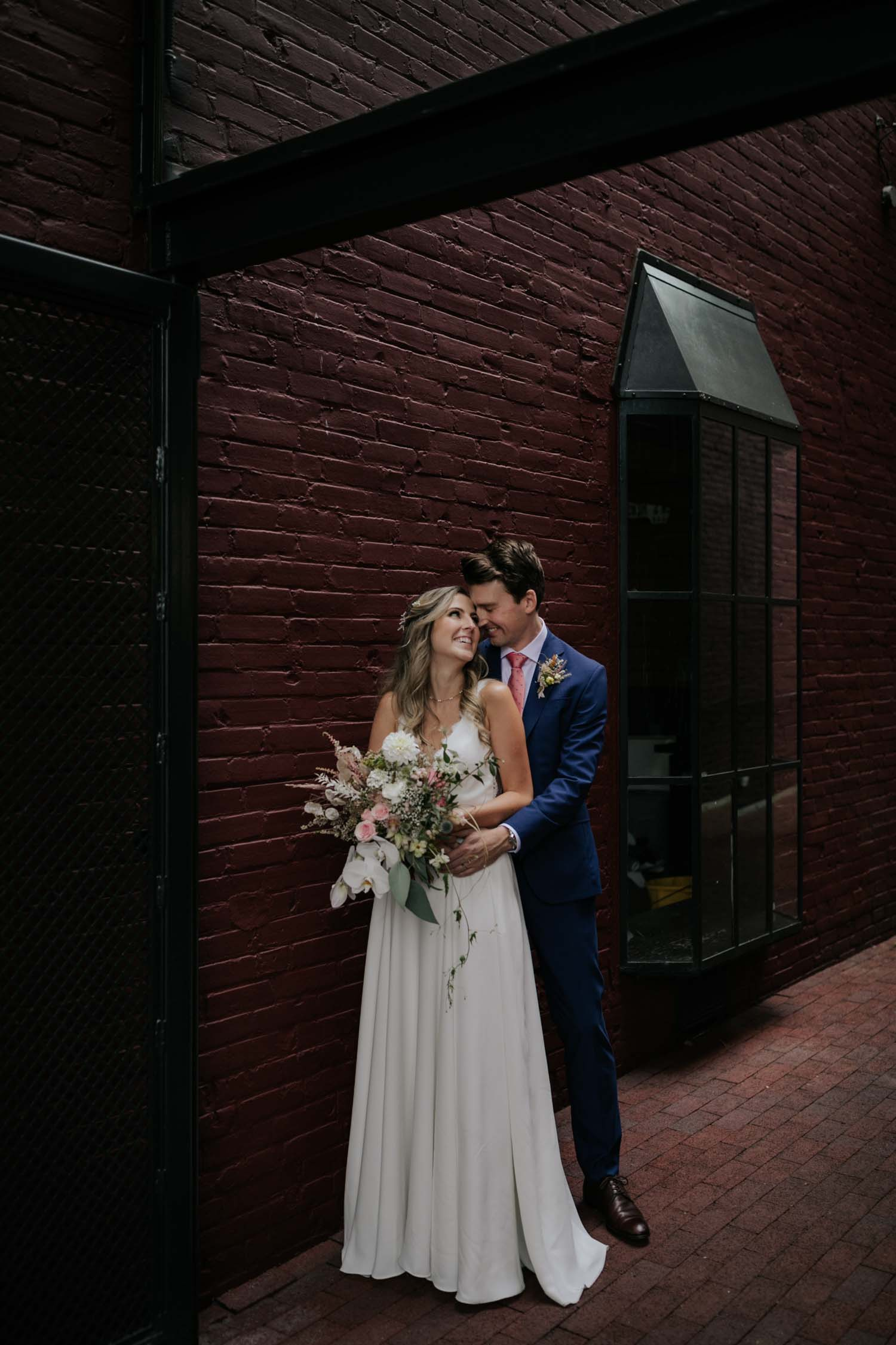 Bride and groom in front of red wall during their couple session on the city streets of Gastown in Vancouver