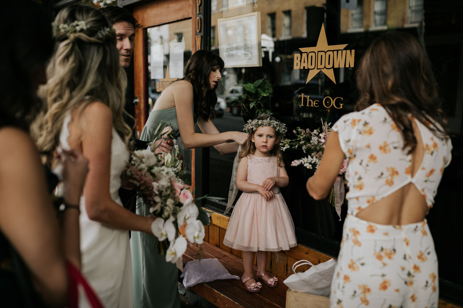 Bridesmaid wearing light green dress puts baby's breath flower crown on top of flower girl's head