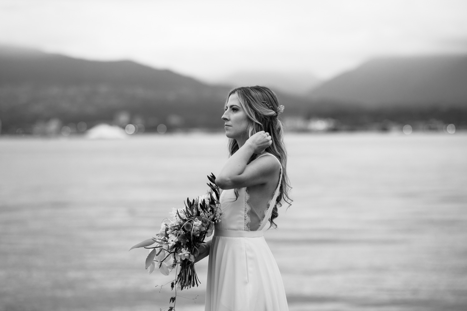 Beautiful bride with long blonde hair wears backless Truvelle wedding dress made by alternative Vancouver wedding dress designer
