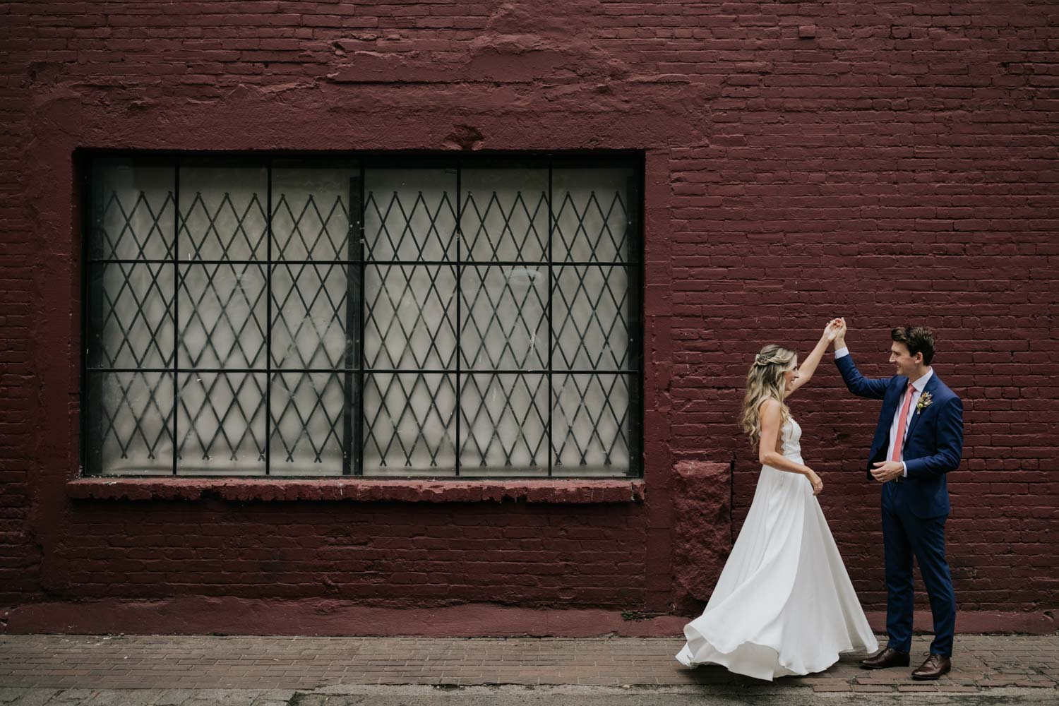 Bride and groom dance in front of red wall during wedding photoshoot on the city streets of Gastown in Vancouver