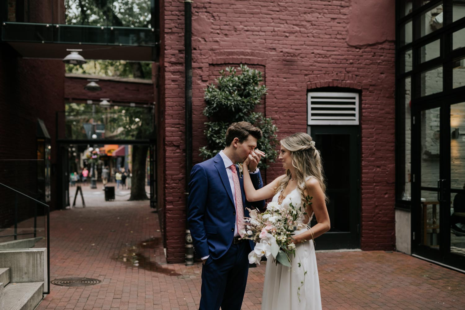 Groom kisses bride's hand in wedding photoshoot on the city streets of Gastown in Vancouver