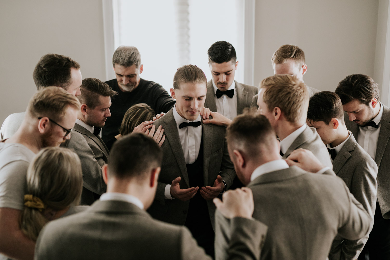 Groomsmen praying from groom