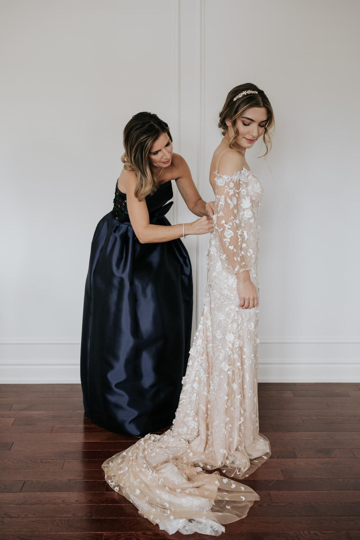 Mom helping bride get ready in her Tara Lauren Wedding Dress