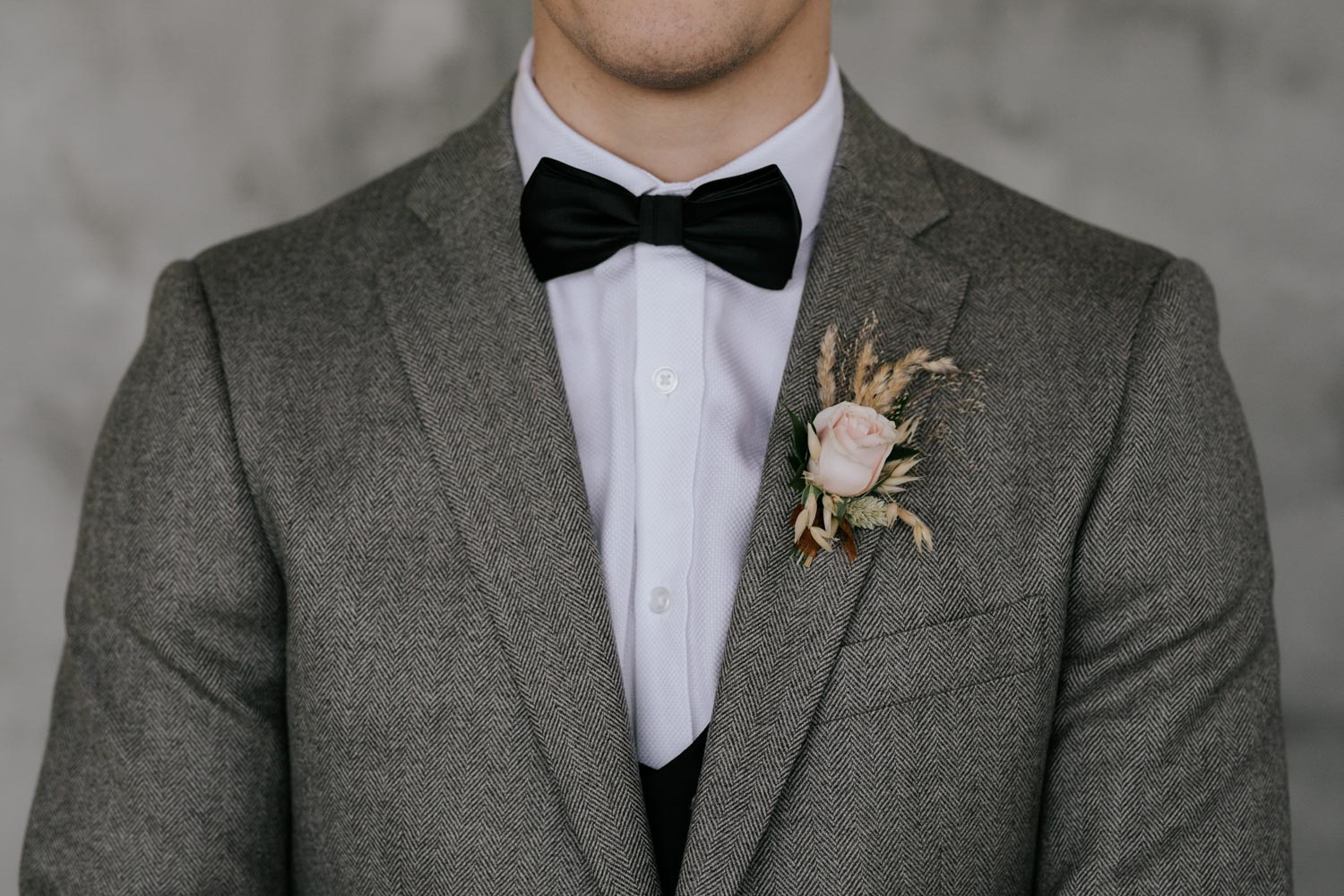 Groom with long hair in grey jacket, black bowtie and black pants